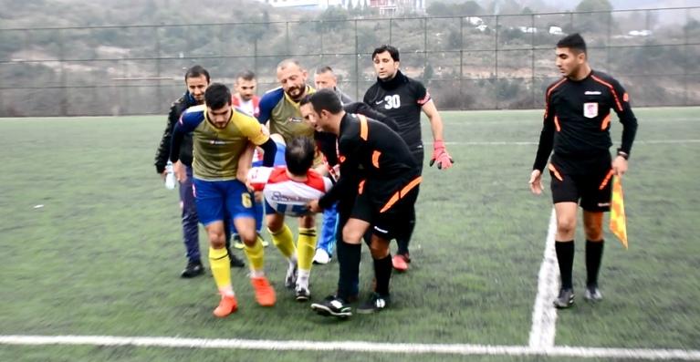 Sakatlanan futbolcuyu hakem ve rakip oyuncular taşıdı